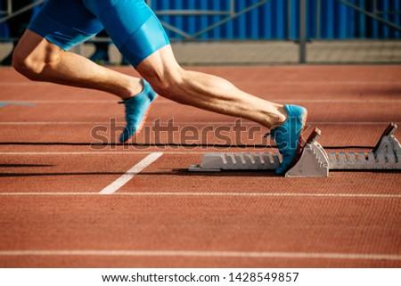 feet runner sprinter fast start to run from starting blocks #1428549857