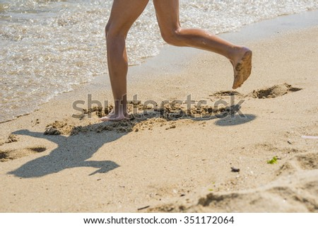 Feet running on the sand. Selective focus on one leg. Blurred sea sand on the beach for texture or background. Bokeh background. #351172064