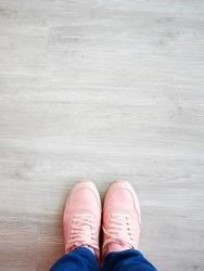 Feet selfie with fashion pink sneaker on wooden background. Top view with copy space