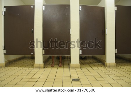 Feet showing under bathroom stall door, in public restroom with four stalls