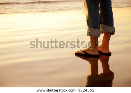 Feet standing at the ocean's edge at sunset