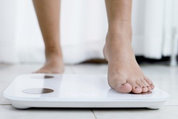 feet standing on electronic scales for weight control. Measurement instrument in kilogram for a diet control