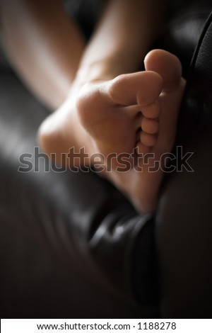 feet up. relaxing on a big, comfy black leather couch
