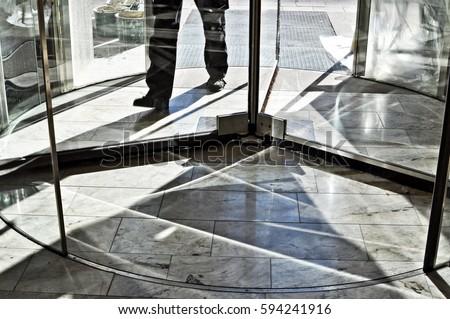 Feet walking in revolving door.