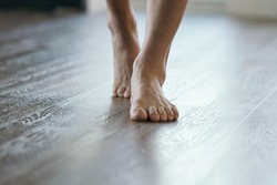 Feet walking on heated floor - wood or vinyl.