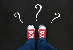 Feet wearing red shoes on black background with question marks. choice concept