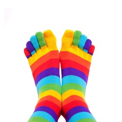 Feet wearing winter colorful striped socks isolated on white background