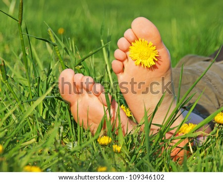 Feet with flower in green grass