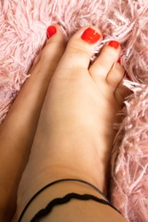 Feet with Red Toenails and Black Anklet on Pastel, Pink Background