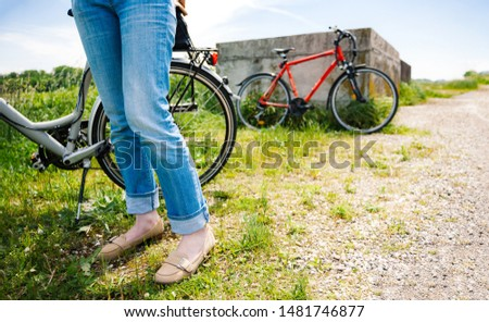 Feets of adult woman in blue jeans denim making a pause after riding the bike on gravel road with orange bike in the background