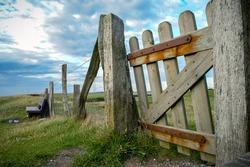 Fehmarn, ein Ort zum ausruhen  - und typisch für diese Ostseeinsel sind die Schafsweiden mit ihren Toren zum passieren. Und natürlich lädt eine Bank am Meer zum verweilen und erholen ein.