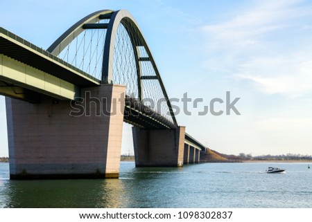 Fehmarn Sound Bridge (German: Fehmarnsundbruecke) and a fast sport boat on the Baltic Sea against a blue sky, vacation travel concept with copy space