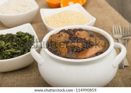 Feijoada - Brazilian beef, sausage, pork and black bean stew served with manioc flour, kale, white rice and oranges.
