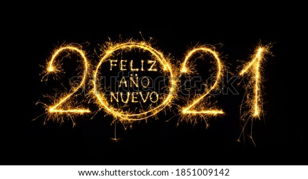 Feliz Ano Nuevo 2021. Creative lettering Happy New Year 2021 Spanish language written sparkling sparklers isolated on black background. Beautiful Glowing overlay template for holiday greeting card. Foto stock ©