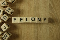 Felony word from wooden blocks on desk