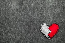 Felt broken heart on gray background, copy space