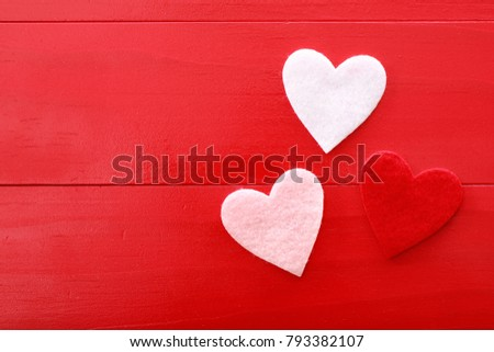 Felt hearts on a red wooden background #793382107