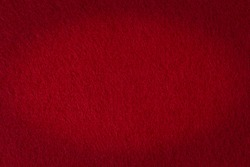 Felt texture with vignetting effect as a background, dark red color.