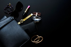 Female accessories, handbag, cosmetics on a black background. Flat lay, top view.