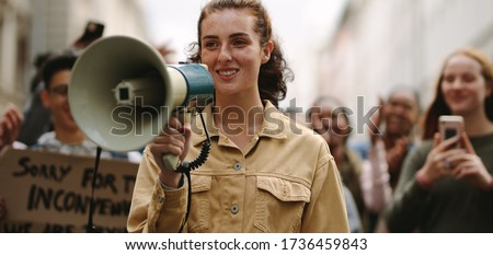 Female activist protesting at a strike, giving slogans with a megaphone. Woman demonstrator protesting with megaphone during a strike.