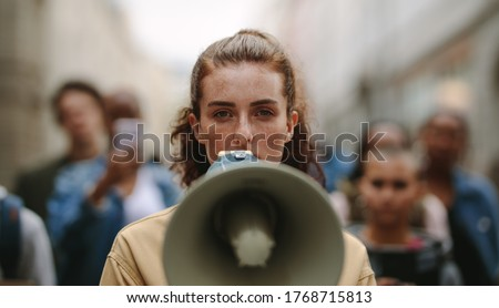 Female activist protesting with megaphone during a strike with group of demonstrator in background. Woman protesting in the city.
