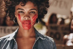 Female activist with a hand print on her mouth, demonstrating violence on women. Woman protesting against domestic violence and abuse with group in background.