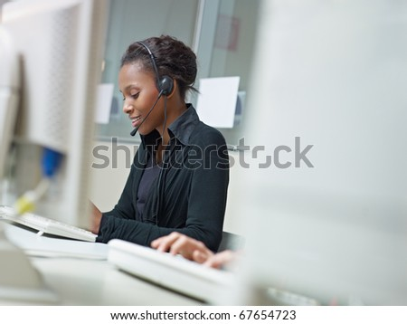 female african american customer service representative talking on the phone and typing on pc. Horizontal shape, side view, copy space