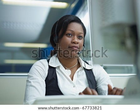 female african american customer service representative talking on the phone and typing on pc. Horizontal shape, front view