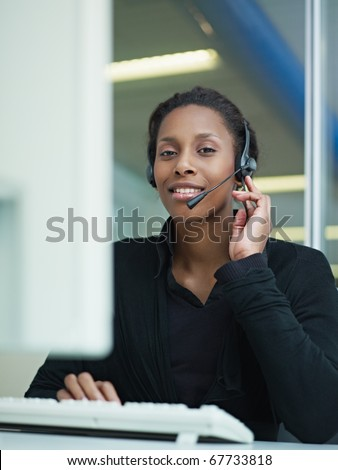female african american customer service representative with headset looking at camera and smiling. Verical shape, front view, waist up