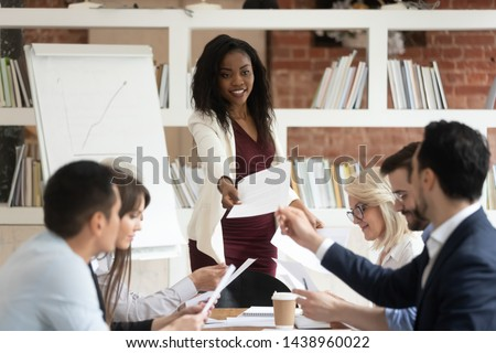Female african coach manager give papers presenting document report business plan to team people at corporate meeting, diverse staff group and black boss do paperwork sit at office conference table