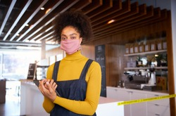 Female African coffee shop owner wearing face mask standing in front of counter with digital tablet.