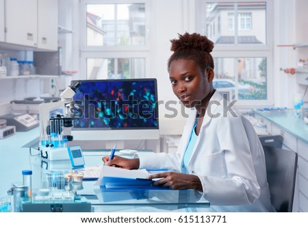 Female African scientist, medical worker, tech or graduate student works in modern biological laboratory. This image is toned.