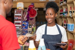 female african shop attendant smiling while collecting money from a customer