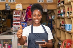 female african store attendant smiling and gives a thumbs up