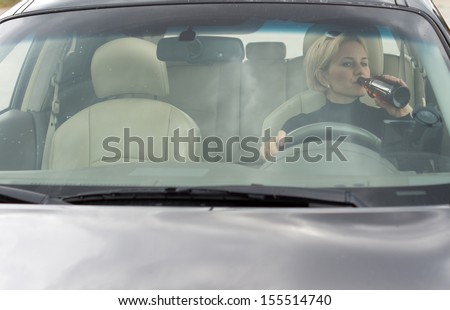 Female alcoholic sitting in her car drinking and driving as she gulps alcohol directly from the bottle, view through the front windscreen