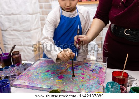 """female and children's hands closeup create a pattern of paints on the surface of the water with a special tool. Ebru Art, the Ancient Techniques of """"Painting on Water"""""""