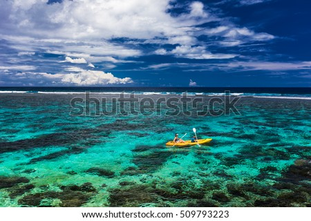 Female and little boy paddling canoe on a lagoon with tropical coral reef
