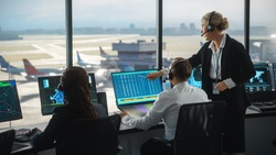 Female and Male Air Traffic Controllers with Headsets Talk in Airport Tower. Office Room is Full of Desktop Computer Displays with Navigation Screens, Airplane Departure and Arrival Data for the Team.
