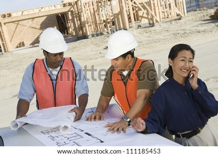 Female and male architects communicating at construction site