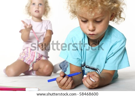 female and male blonde caucasian adorable kids play with color pens