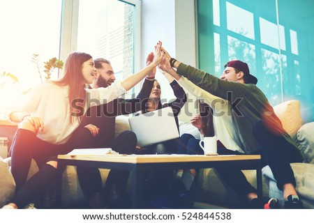 Female and male classmates celebrating pathing math examination, feeling exciting and cheerful , giving high five during informal meeting in friendly atmosphere with modern laptop in coworking space