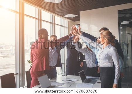 Female and male classmates celebrating pathing math examination, feeling exciting and cheerful , giving high five during informal meeting in friendly atmosphere with modern laptop in coworking space #670887670