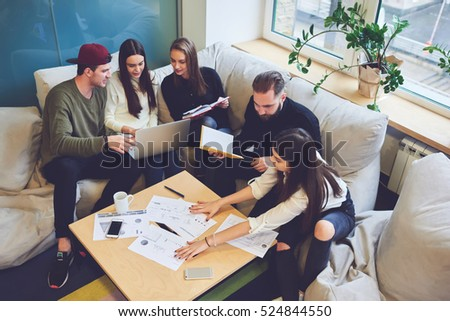 Female and male classmates doing homework for business course, accounting data, making graphic illustrations during informal meeting in friendly atmosphere with modern laptop in coworking space