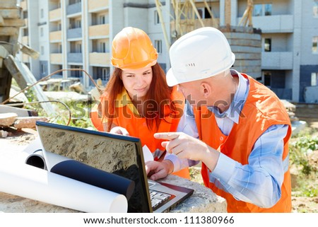 female and male construction workers looking at laptop