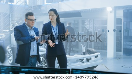 Female and Male Engineer Walk in a High Tech Development Facility Holding a Tablet Computer and Pass an Electric Car Chassis Prototype with Batteries and Wheels.