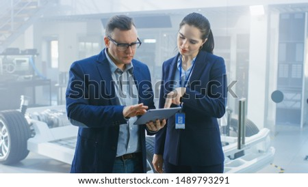 Female and Male Engineer Work in a High Tech Development Facility Holding a Tablet Computer. They Stand Next to an Electric Car Chassis Prototype with Batteries and Wheels.