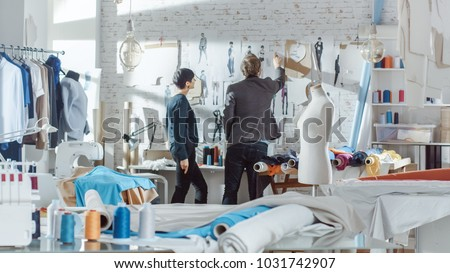 Female and Male fashion, designer,  Choosing and Pinning  to the Wall Clothing Sketches for Their New Collection. Studio is Sunny. Colorful Fabrics, Clothes Hanging and Sewing Items are Visible.