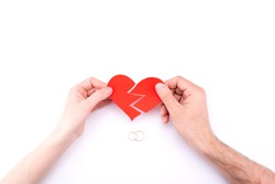 Female and male hands hold a broken heart on a white background with wedding rings. Marriage problems, divorce