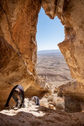 Female and male hikers descending  a steep and hard hiking trail. Extreme and dangerous climbing and adrenaline. Amazing mountain landscape in Negev Desert National Park, Israel.