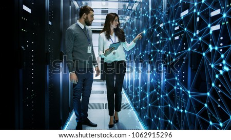Female and Male IT Engineers Discussing Technical Details in a Working Data Center/ Server Room with Internet Connection Visualisation.